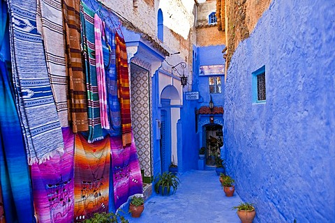Narrow alleyway in Chefchaouen, walls and footpath are painted in blue, colourful blankets for sale hanging on the wall, Rif Mountains, northern Morocco, Morocco, Africa
