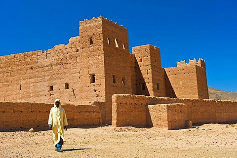 Berber man wearing a traditional djellabah walking in front of Taouirt Kasbah, mud fortress, mud brick building of the Berber tribes, Tighremt, Draa Valley, Southern Morocco, Morocco, Africa