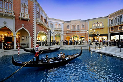 Gondolier in a gondola to attract tourists in simulated Venetian alleys under an artificial sky, Canale Grande, 5-star luxury hotel, The Venetian Casino, Las Vegas, Nevada, United States of America, USA