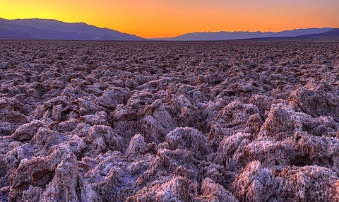 Spectacular lighting after sunset, salt crust on the Devil's Golf Course, Panamint Range, Black Mountains, Death Valley National Park, Mojave Desert, California, United States of America, USA