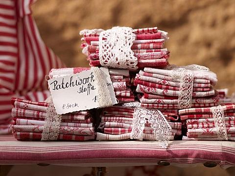 Patchwork fabrics on a craft market at a garden festival at Schloss Buedingen, Hesse, Germany, Europe