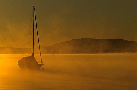 Boat in the early morning on lake Chiemsee, Chiemgau, Upper Bavaria, Germany, Europe