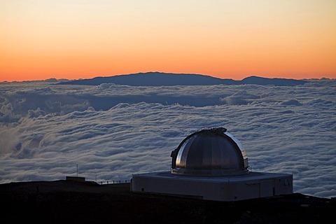 Infrared Telescope Facility, IRTF, telescope for infrared astronomy at the Mauna Kea Observatory on the summit of the Mauna Kea volcano, 4205m, with clouds below, summit of the Haleakala volcano on the Island of Maui at back, Mauna Kea, Hawaii, USA