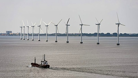Cargo ship sailing in front of an offshore wind farm in the oresund outside Copenhagen, Denmark, Europe