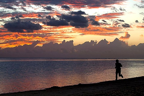 Man jogging at sunset on the beach of Saline-les-Bains, La Reunion island, Indian Ocean
