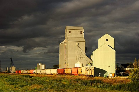 Typical granary with train and storm clouds, Manitoba, Canada