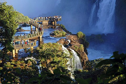Footbridge with tourists at the Iguazu Falls at the border between Argentine and Brazil