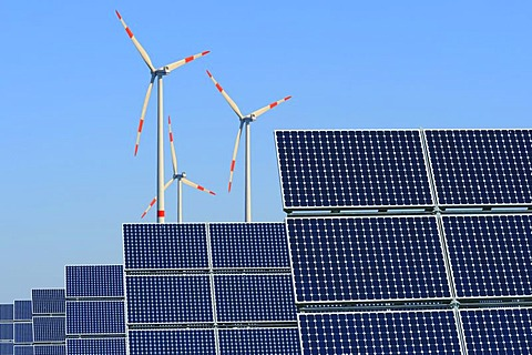 Renewable energy, solar panels in front of wind turbines, composing