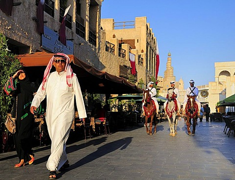Man wearing a traditional Thobe and mounted police in front of the tower of the Islamic Cultural Centre FANAR, Souk Waqif, Doha, Qatar, Middle East