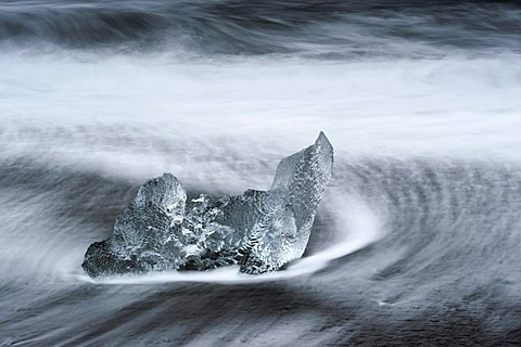 Melting icebergs lying in the strong surf on the black volcanic beach at Joekulsarlon, Iceland, Europe
