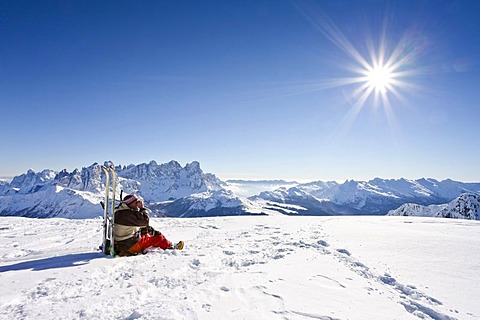 Snowshoe walker having a break on the summit of Uribrutto mountain, above Passo Valles mountain pass, Dolomites, Palla group and Passo Rolle mountain pass at the back, province of Trento, Italy, Europe