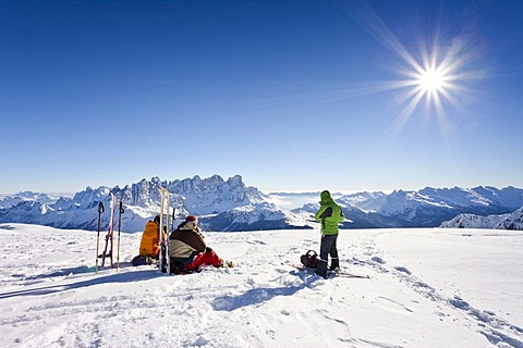 Mountaineers taking a break on the summit of Uribrutto mountain above Passo Valles, Dolomites, Palla group and Passo Rolle mountain at the back, province of Trento, Italy, Europe