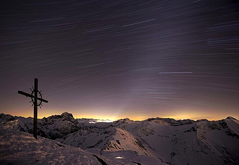 Mountain panorama with a starry sky and summit cross at the blue hour in winter, Baad, Kleinwalsertal, Vorarlberg, Austria, Europe