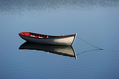 Empty boat on water with reflection, Newfoundland, Canada, North America