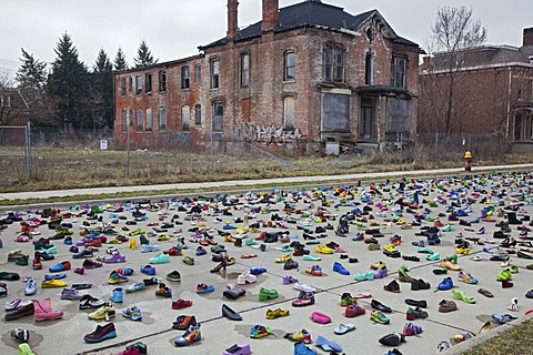 "An art exhibit of thousands of shoes on the street by artist Tyree Guyton called ""Street Folk"" represents the issue of homelessness, part of Art X Detroit, a collection of performance art, music, and literary events held in Detroit, Michigan, USA, America"