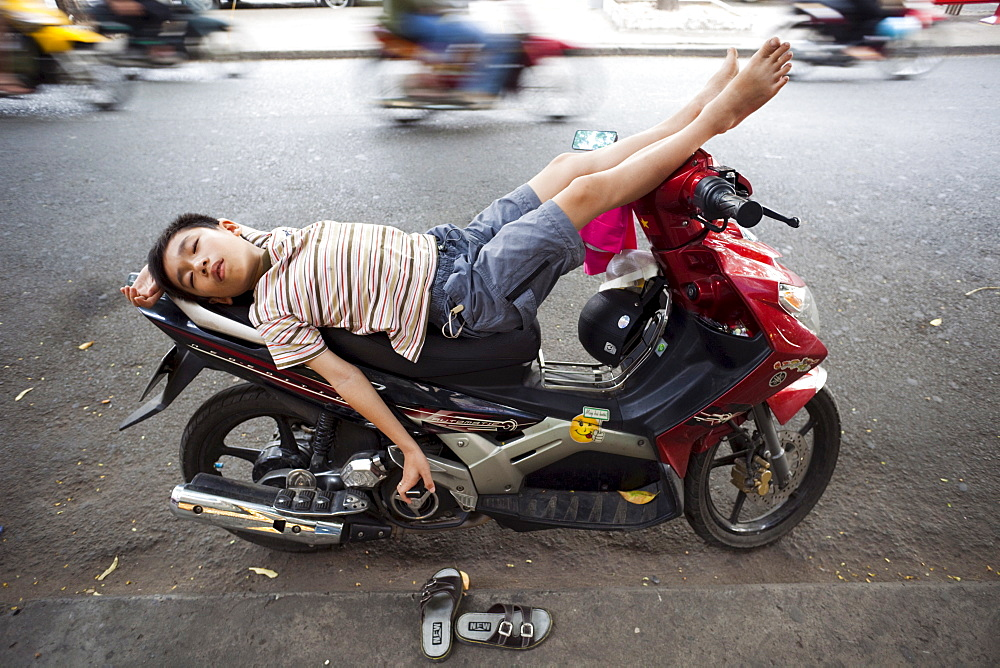 Boy sleeping on motorbike, Ho Chi Minh City, Vietnam, Indochina, Southeast Asia, Asia