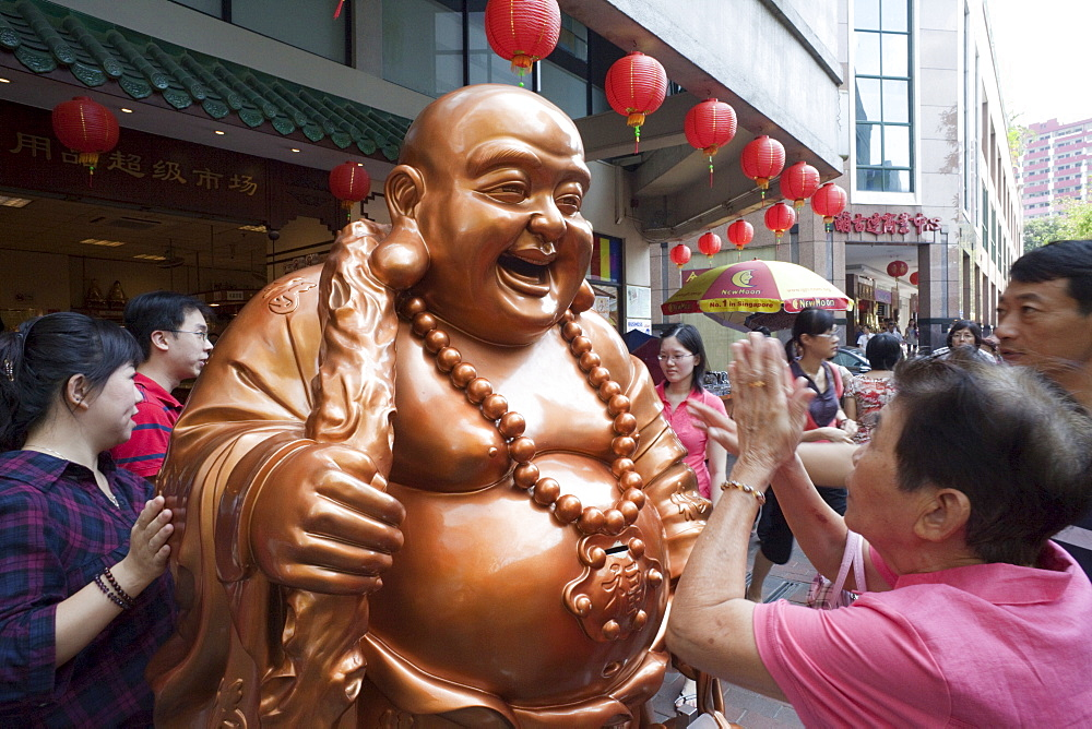 Woman praying to Buddha statue for good fortune, Chinatown, Singapore, Southeast Asia, Asia