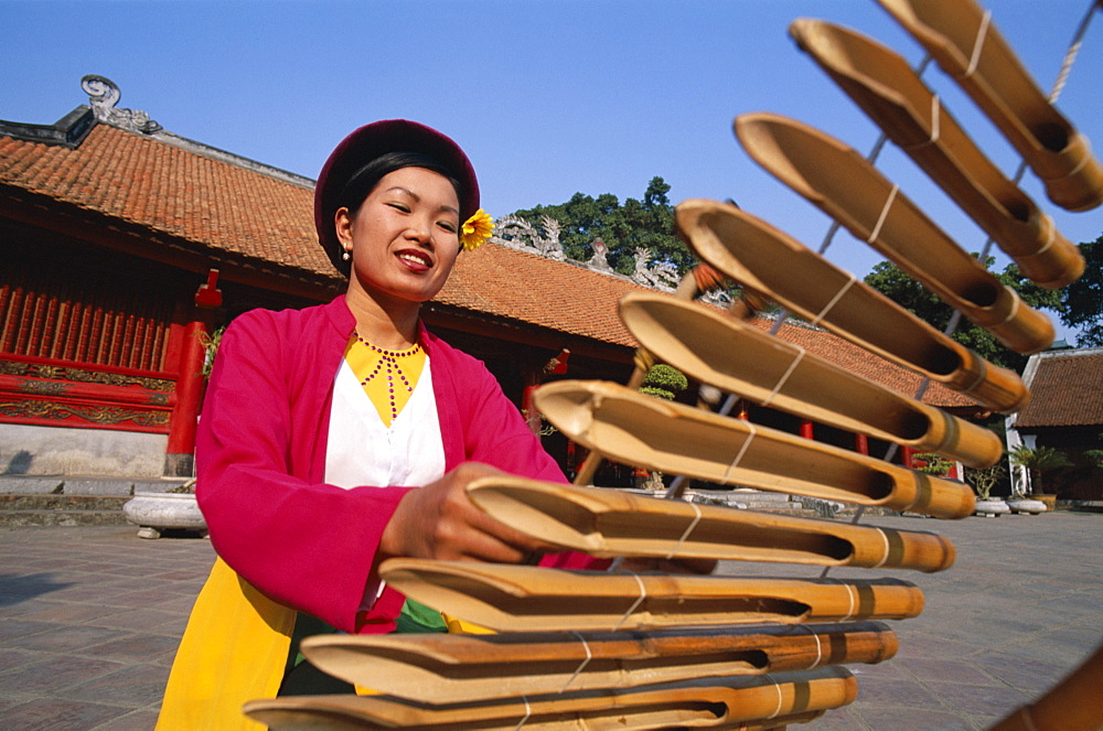 Woman dressed in traditional costume playing a lithophone, a bamboo musical instrument, Temple of Literature, Hanoi, Vietnam, Indochina, Southeast Asia, Asia