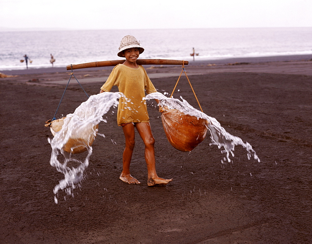 Young boy throwing sea water onto sand to make salt, Bali, Indonesia, Southeast Asia, Asia