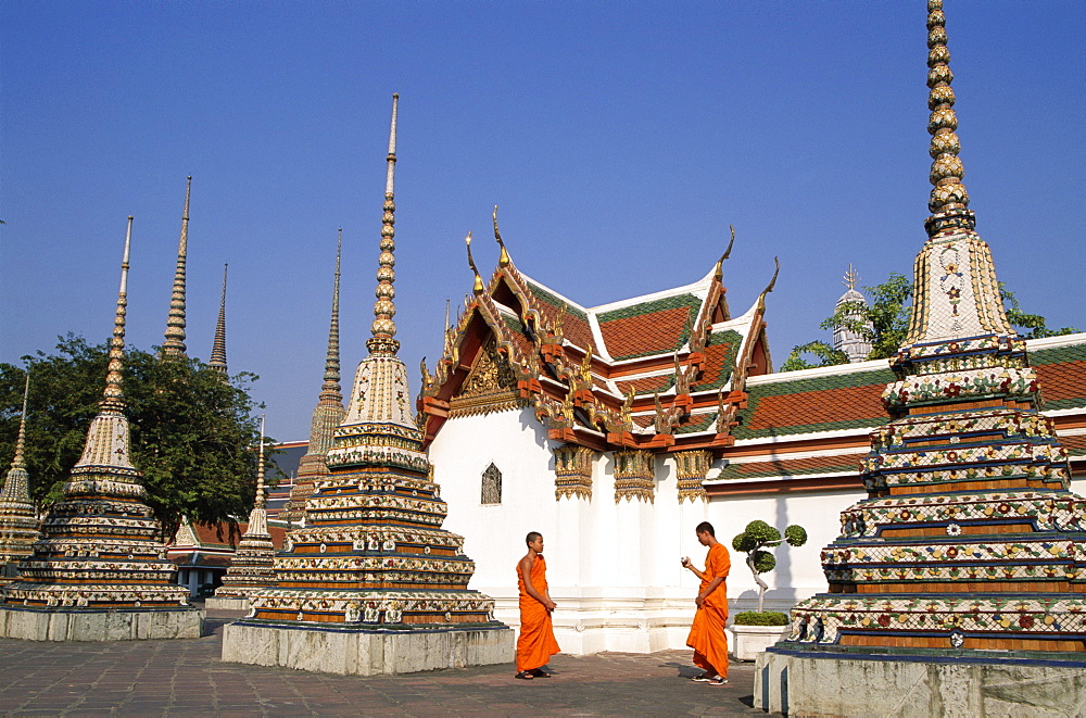 Monks walking past chedis, Wat Pho, Bangkok, Thailand, Southeast Asia, Asia