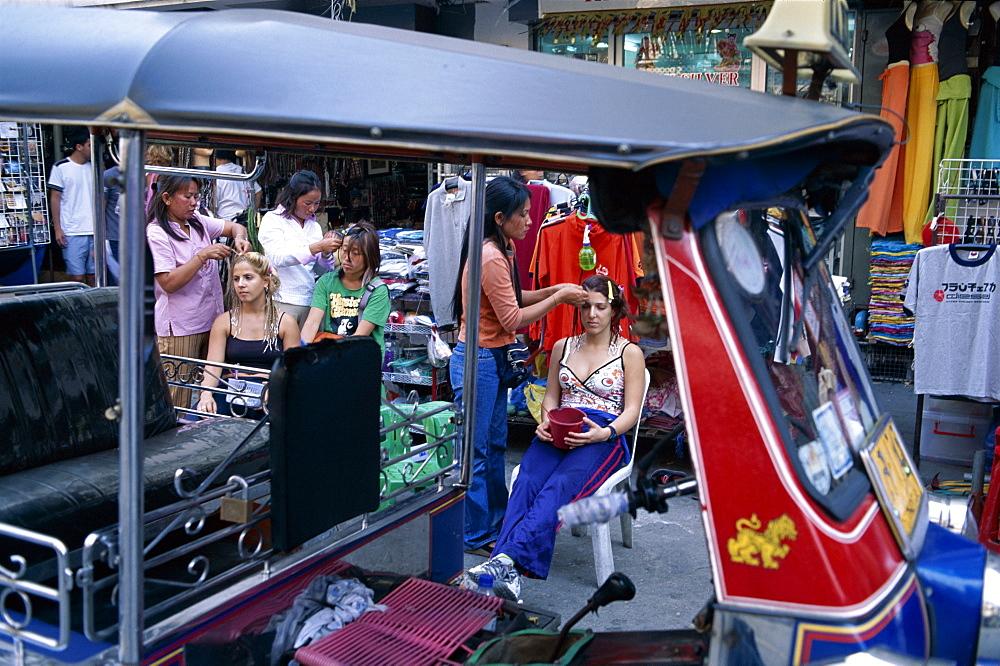 Tourists having their hair braided on Khao San Road, Bangkok, Thailand, Southeast Asia, Asia