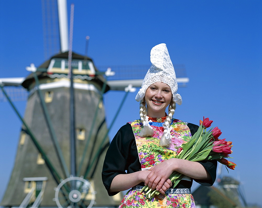 Girl dressed in Dutch costume in front of windmill, Zaanse Schans, Holland (Netherlands), Europe