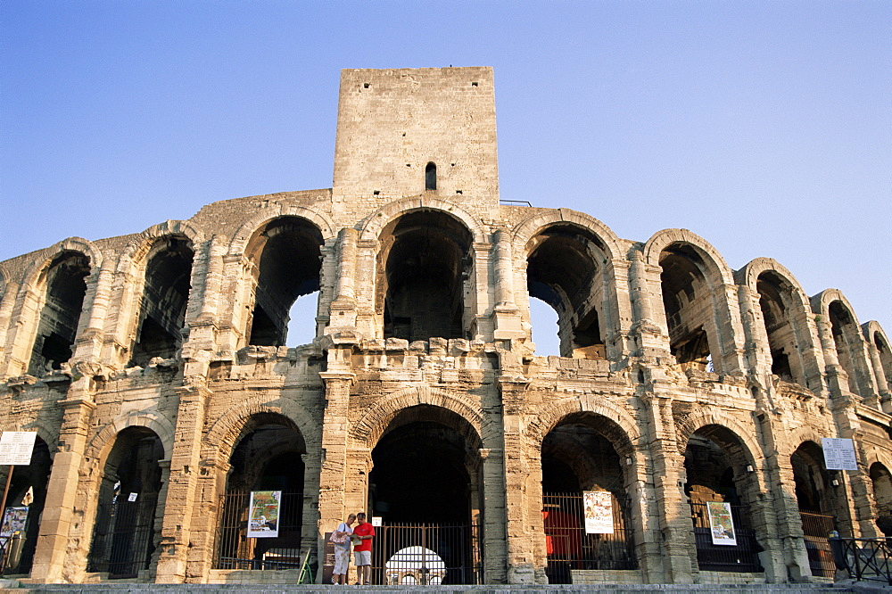 Couple looking at map in front of Roman amphitheatre, UNESCO World Heritage Site, Arles, Provence, France, Europe