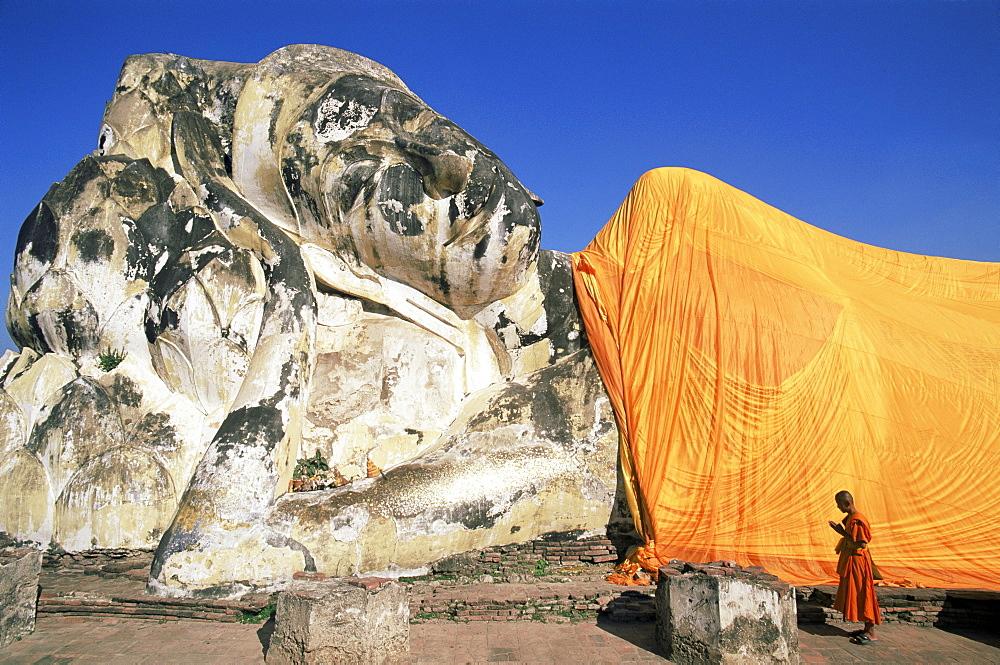 Monk praying at giant reclining Buddha statue, Wat Lokaya Sutha, Ayutthaya Historical Park, Ayutthaya, Thailand, Southeast Asia, Asia
