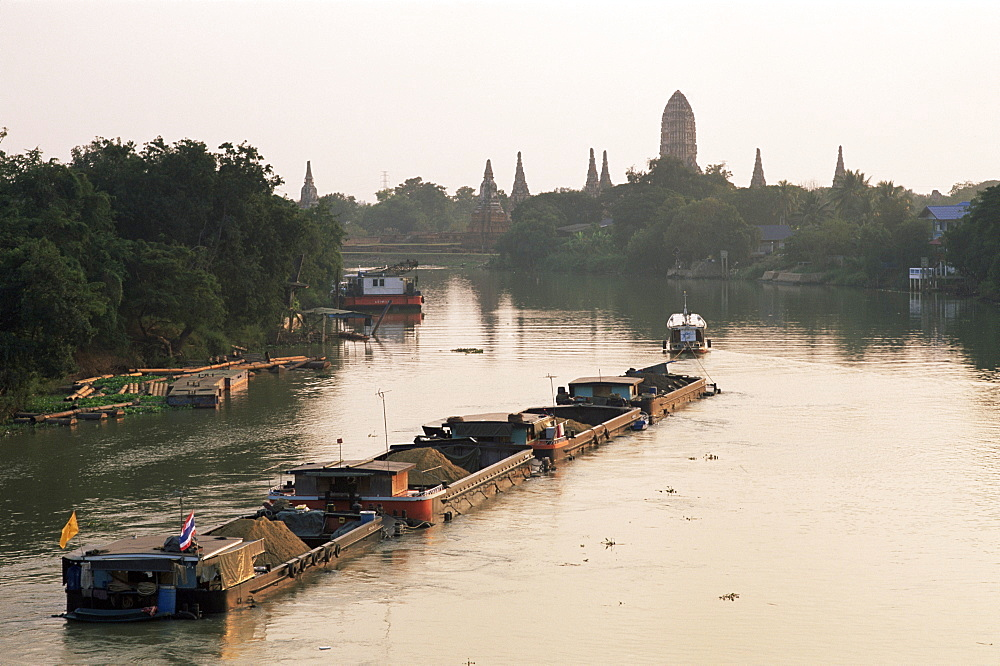 Barges on Chao Phraya River and Wat Chai Wattanaram in background, Ayutthaya Historical Park, Ayutthaya, Thailand, Southeast Asia, Asia