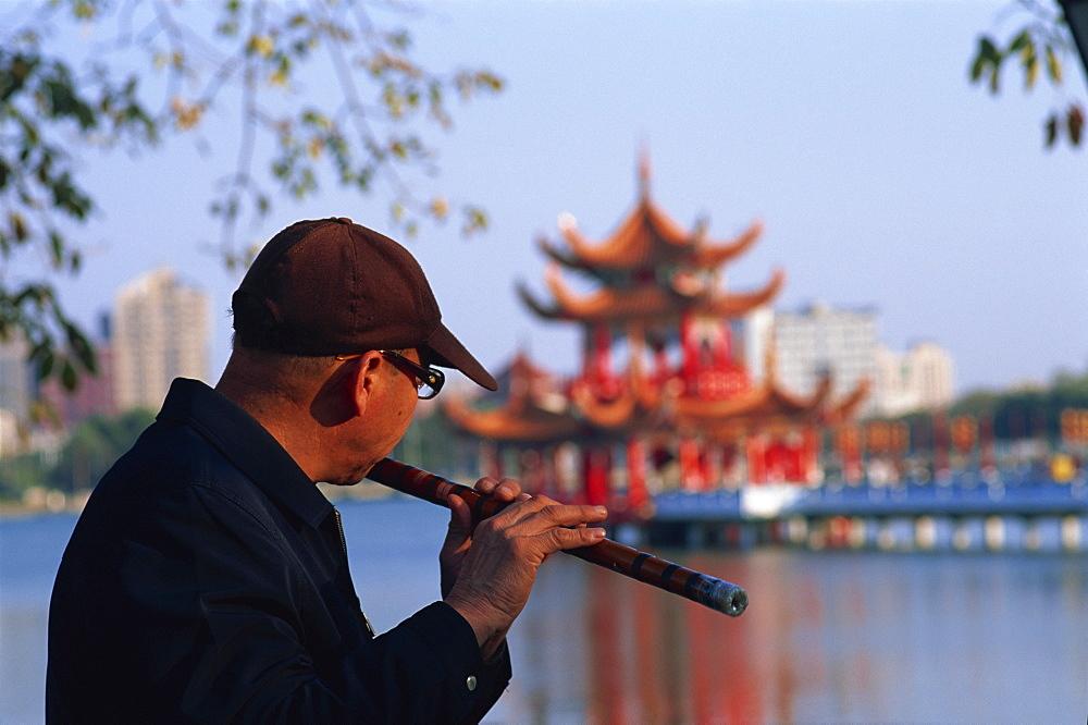 Man playing flute at Lotus Lake, Kaohsiung, Taiwan, Asia
