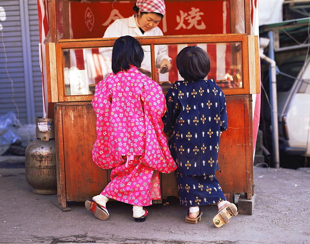 Children dresssed in Yukata at outdoor food stall, Tokyo, Japan, Asia