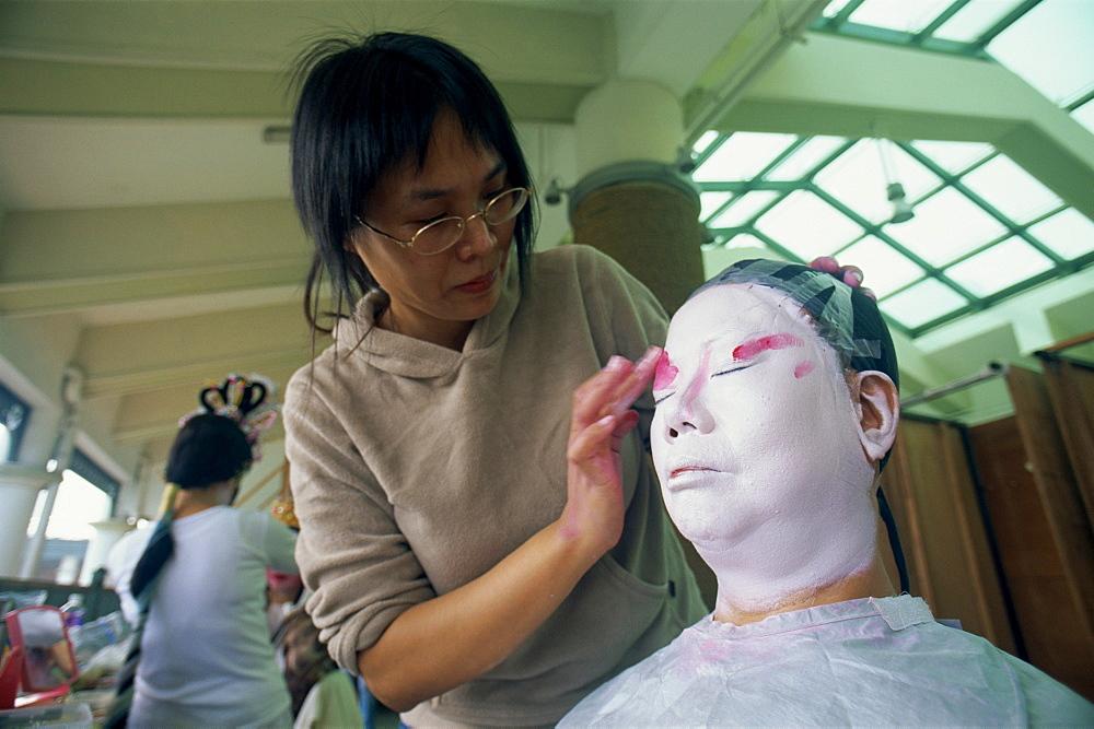 Woman applying make-up to Chinese Opera actor, Hong Kong, China, Asia