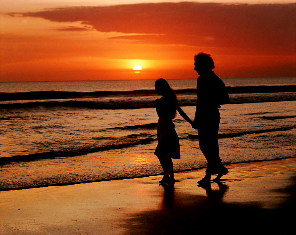 Sunset over sea and silhouette of couple walking on beach - 834-714