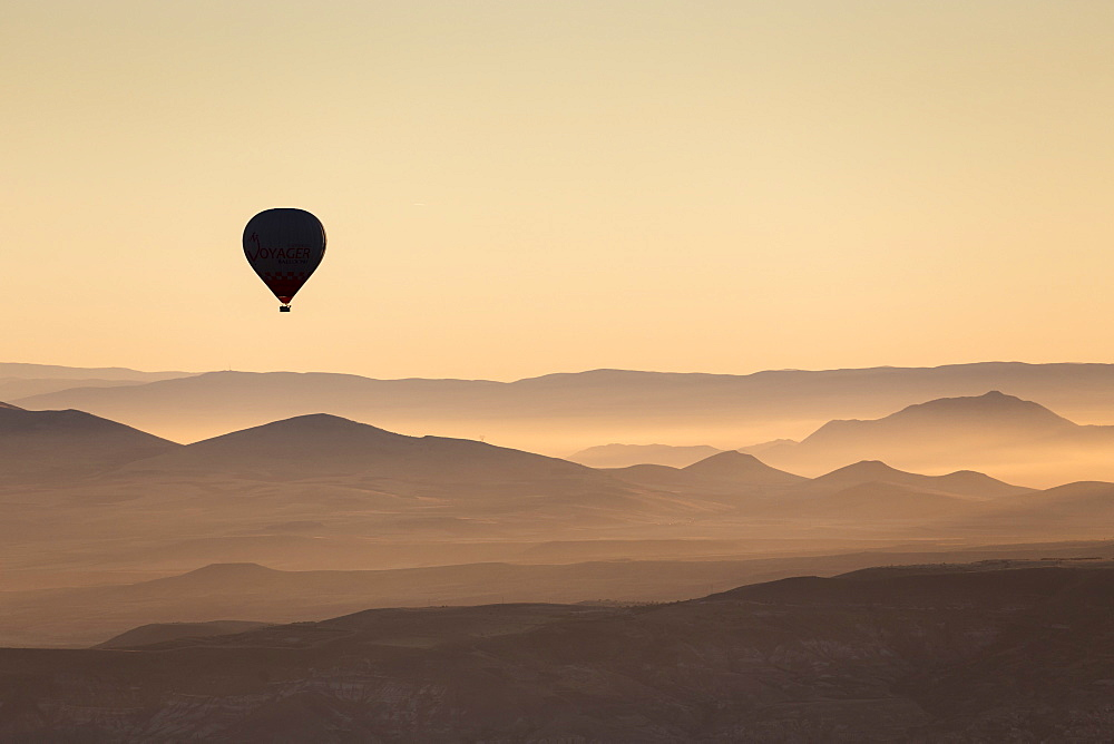 Single hot air balloon over a misty dawn sky, Cappadocia, Anatolia, Turkey, Asia Minor, Eurasia - 835-84
