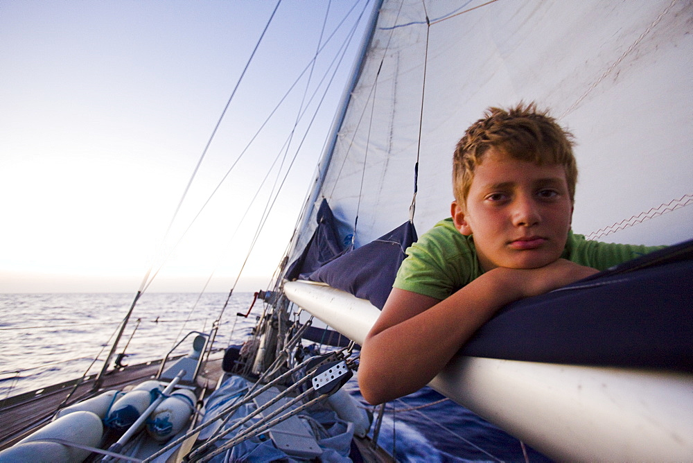 Young boy lying on the main sail of a sailing boat on the Mediterranean sea - 837-1021