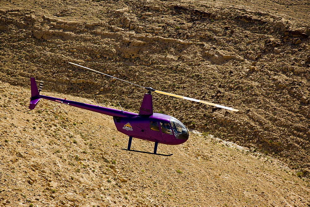 A Robinson R44 helicopter flying over the Negev desert - 837-1093