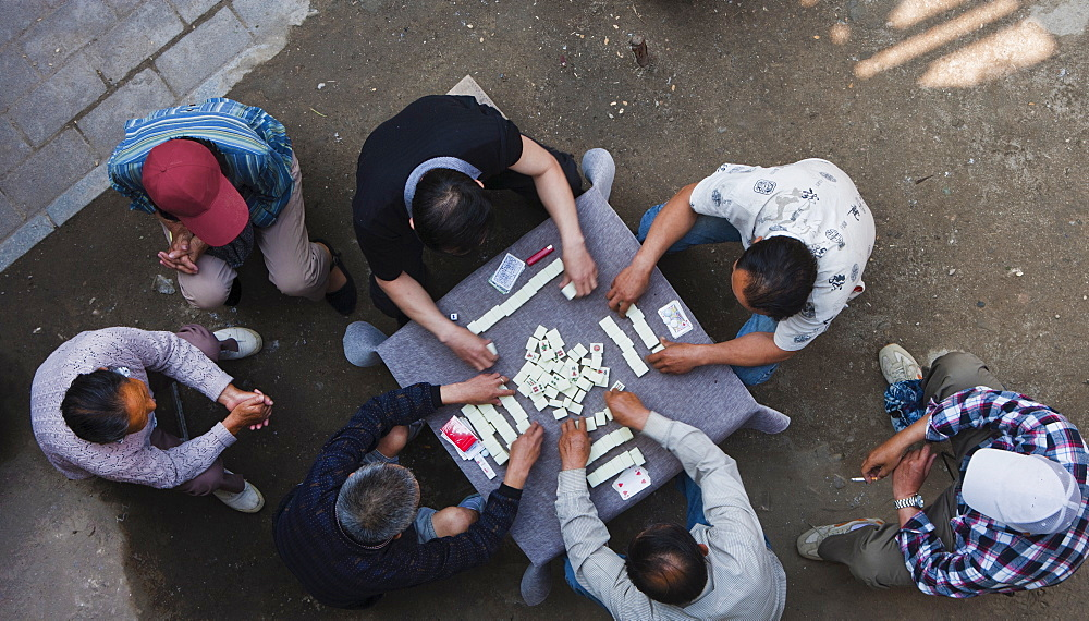 Overhead view of Chinese men sitting outdoors playing the traditional game of mahjong, Hangzhou, China, Asia