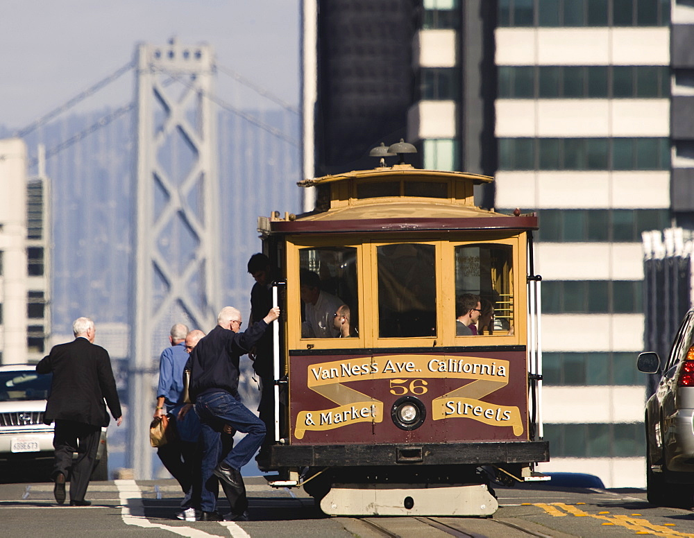 Cable car and passengers on Nob Hill along California Street, with west span of the Bay Bridge in background, San Francisco, California, United States of America, North America - 839-29