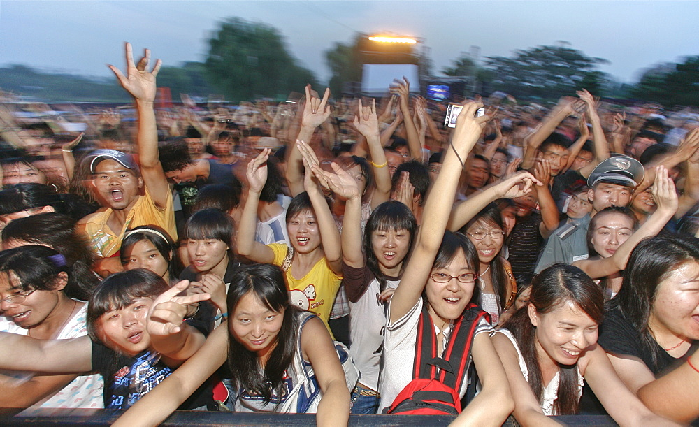 Young Chinese persons cheering at a rock and roll concert, Beijing, China, Asia