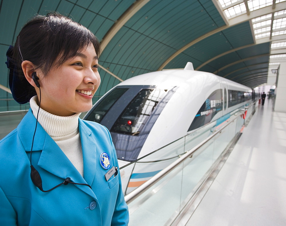 A smiling female attendant wearing a mobile phone earplug standing next to a Magnetic Levitation train on railway platform in Shanghai, China, Asia - 839-35