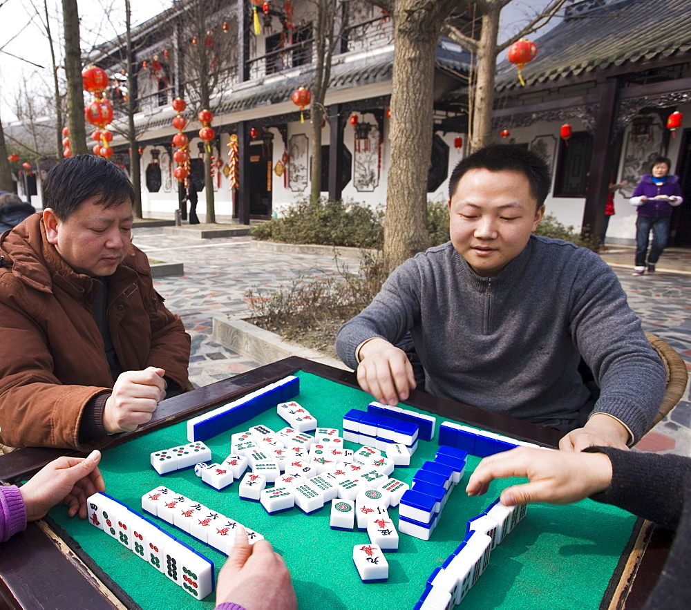 Chinese men playing traditional game of mahjong in a hotel courtyard decorated with red lanterns during Chinese New Year, Chengdu, Sichuan, China, Asia - 839-45