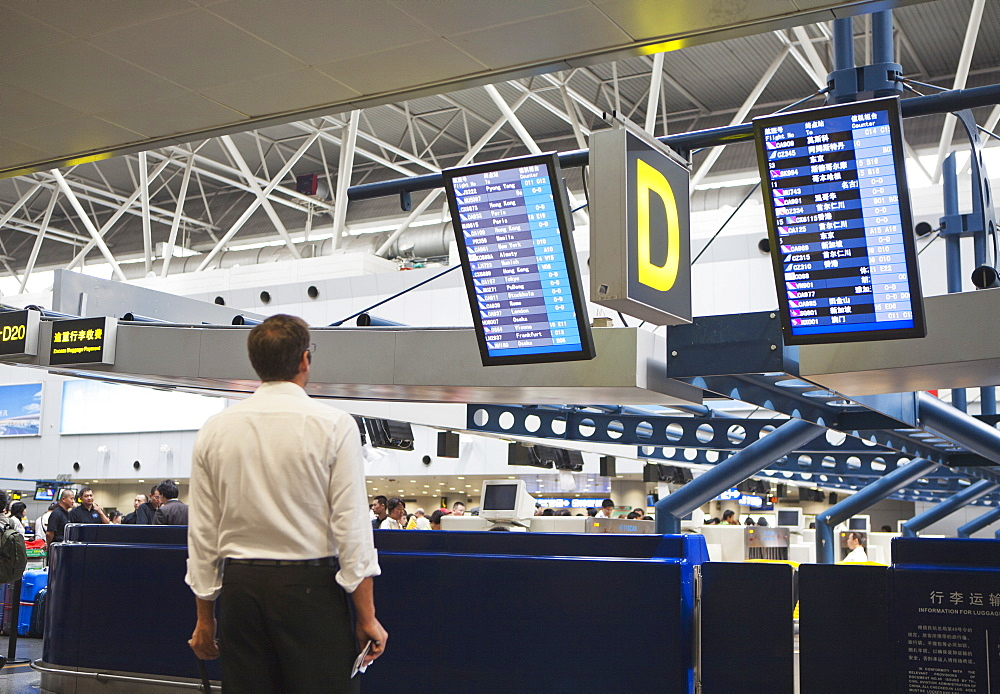 A airline traveler in an airport reading the plane departure signage, Beijing, China, Asia - 839-50