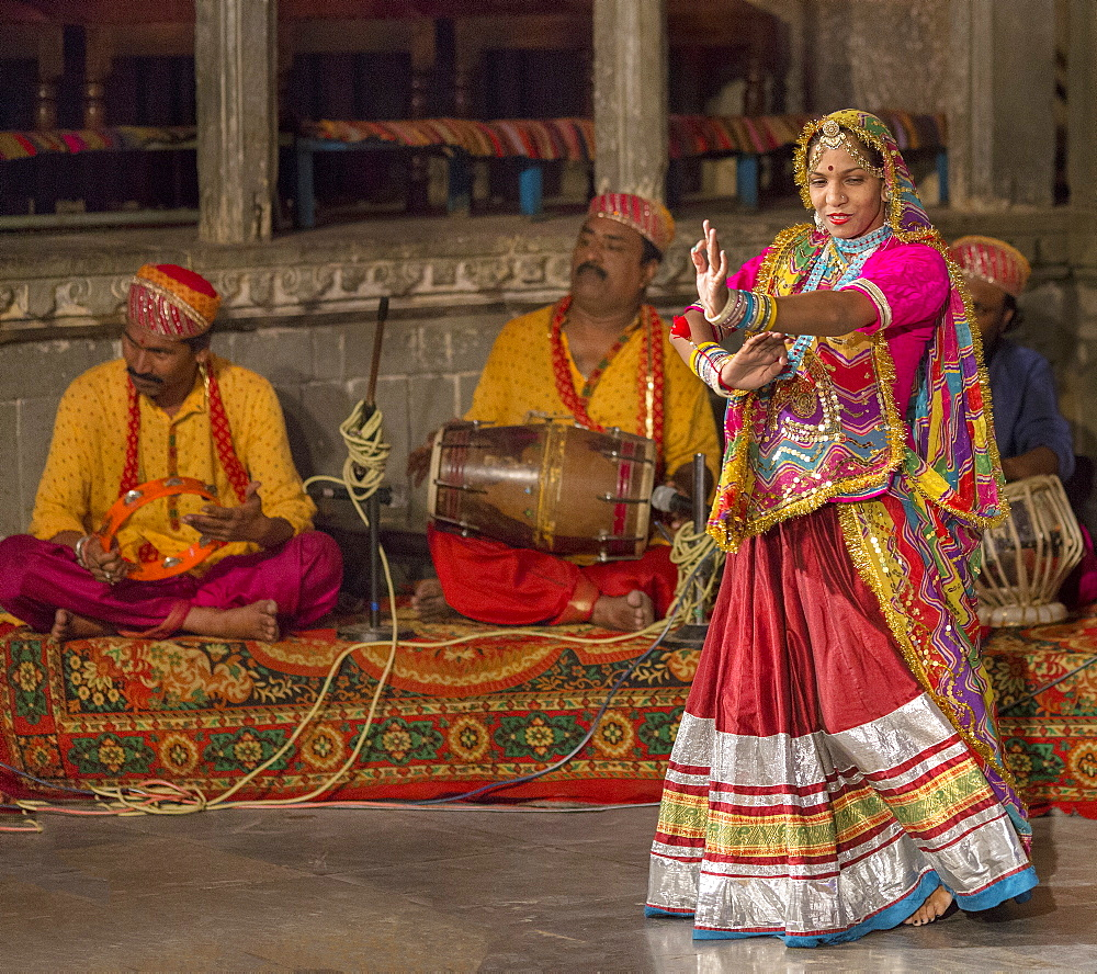 An Indian woman wearing a multi-coloured costume performs a Rajasthani folk dance, with musicians playing acoustic instruments, Udaipur, Rajasthan, India, Asia
