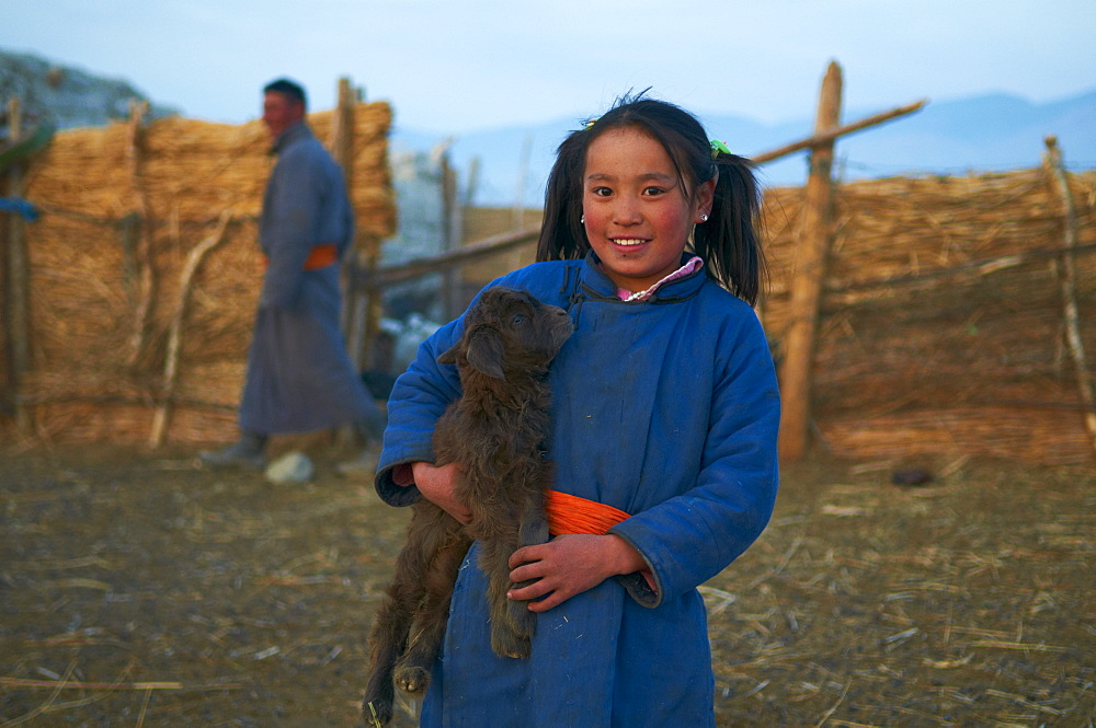 Young Mongolian girl in traditional costume (deel) with her goat, Province of Khovd, Mongolia, Central Asia, Asia