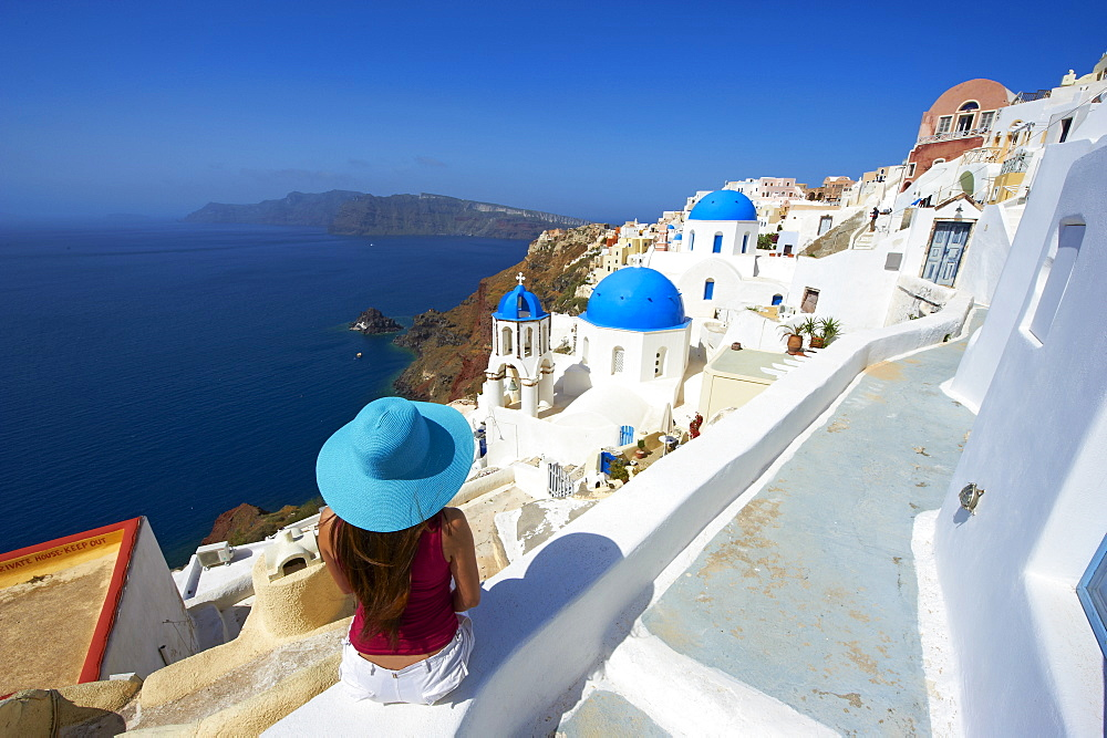 Tourist and church with blue dome, Oia (Ia) village, Santorini, Cyclades, Greek Islands, Greece, Europe
