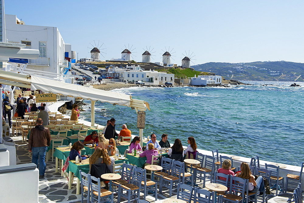 Cafe bar on the sea side with the five windmills (Kato Mili) beyond, Little Venice, Mykonos Town, Chora, Mykonos Island, Cyclades, Greek Islands, Greece, Europe