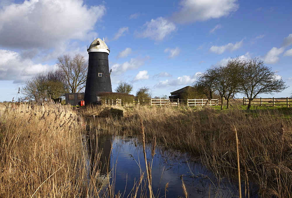 A bright winter day in the Norfolk Broads showing Tall Mill near Upton, Norfolk, England, United Kingdom, Europe