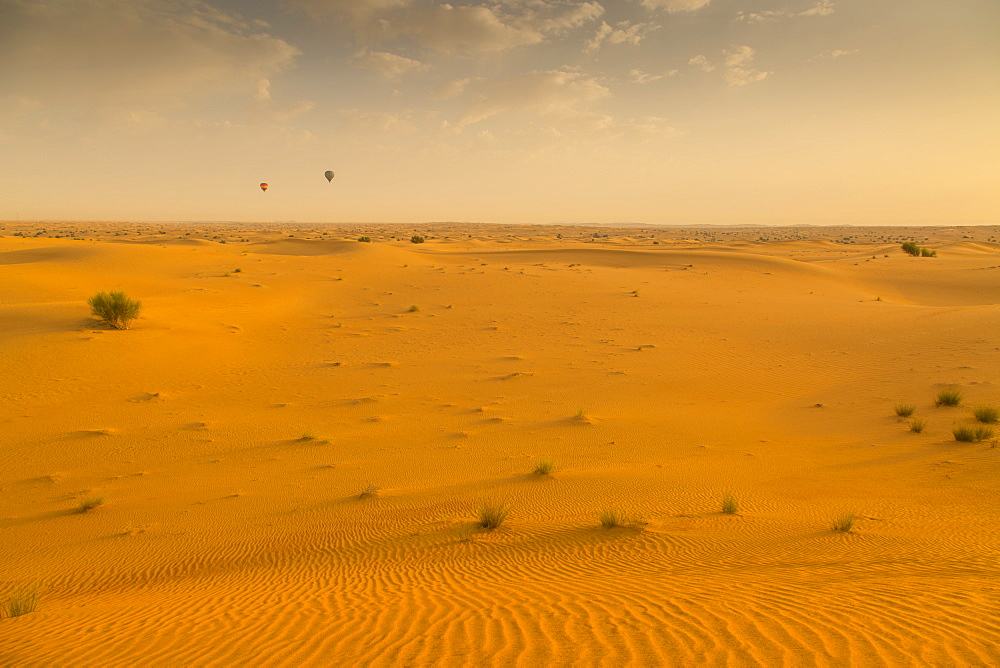 Hot air balloons over sand dunes at sunrise in the Dubai Desert, Dubai, United Arab Emirates, Middle East
