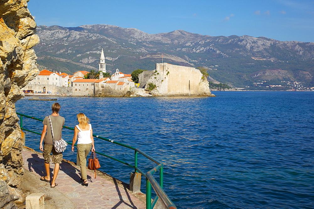 Couple walking along coast towards Old Town, Budva, Montenegro, Europe