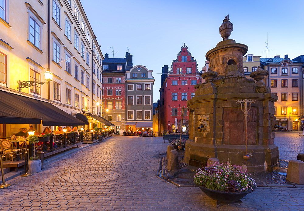 Restaurant and colourful buildings on Stortorget, Old Town Square in Gamla Stan at dusk, Stockholm, Sweden, Scandinavia, Europe